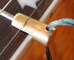 Fifth string capo for the banjo, machined out of brass.  A world's first.